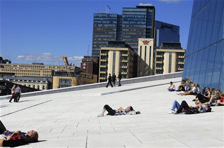 People sunbathe in front of the Oslo Opera House, the home of the Norwegian National Opera and Ballet, in Oslo June 20, 2012. REUTERS/Cathal McNaughton