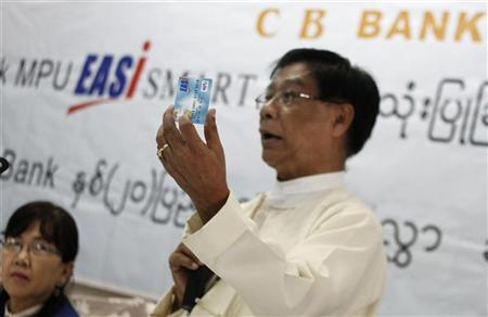 Phay Myint (R), managing Director of the CB Bank, displays a new debit card to the public and the media in Yangon September 14, 2012. REUTERS/Minzayar