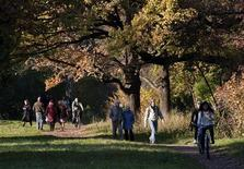 Люди гуляют по парку осенним днем в Москве, 10 октября 2010 года. Рабочая неделя в Москве будет облачной, но осадки в столице маловероятны, прогнозируют синоптики. REUTERS/Nikolai Korchekov