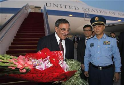 U.S. Secretary of Defense Leon Panetta is welcomed with a bouquet of flowers as China's Chief of the General's Staff Ma Xiao Tian (R) and U.S. Ambassador to China Gary Locke (C) look on at Beijing International Airport, September 17, 2012. Panetta is on the second official stop of a three nation tour to Japan, China and New Zealand. REUTERS/Larry Downing