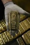 Мужчина держит слиток золота на заводе в швейцарском городке Мендризио, 13 ноября 2008 года. Цены на золото близки к максимуму семи месяцев благодаря обещанию ФРС США держать процентные ставки на низком уровне. REUTERS/Arnd Wiegmann