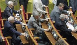 Депутаты от Партии регионов голосуют во время заседания Рады в Киеве, 5 июня 2012 года. Верховная Рада Украины, в которой сторонники президента страны Виктора Януковича надеются сохранить большинство по итогам назначенных на 28 октября выборов, вернула правительству на доработку проект госбюджета 2013 года, основные показатели которого аналитики и оппозиция назвали нереалистичными. REUTERS/Gleb Garanich