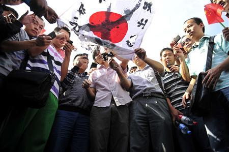 Demonstrators burn a crossed-out Japanese national flag during a protest in Xi'an, Shaanxi province September 15, 2012. Thousands of Chinese besieged the Japanese embassy in Beijing on Saturday, hurling rocks, eggs and bottles with protests reported in other major cities in China amid growing tension between Asia's two biggest economies over a group of disputed islands. REUTERS/Rooney Chen