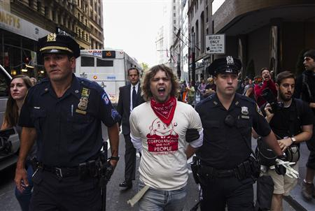 An Occupy Wall Street activist is escorted by New York Police Department officers after being arrested while demonstrating in the financial district during the one-year anniversary of the movement in New York, September 17, 2012. REUTERS/Lucas Jackson