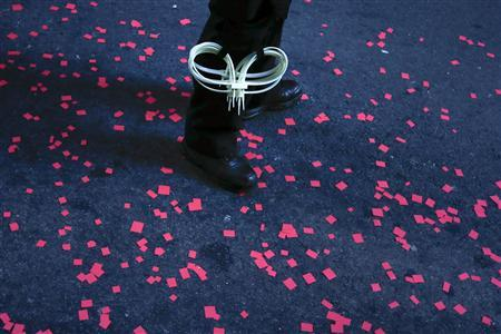 A policeman stands guard near Occupy Wall Street activists who sprayed confetti while matching past the financial district in Lower Manhattan on the one-year anniversary of the movement in New York on September 17, 2012. REUTERS/Adrees Latif