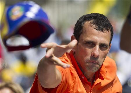 Opposition candidate Henrique Capriles throws his cap to supporters during an election rally in Caracas September 16, 2012. REUTERS/Carlos Garcia Rawlins
