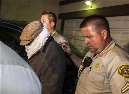 Nakoula Basseley Nakoula (L) is escorted out of his home by Los Angeles County Sheriff's officers in Cerritos, California September 15, 2012. REUTERS/Bret Hartman