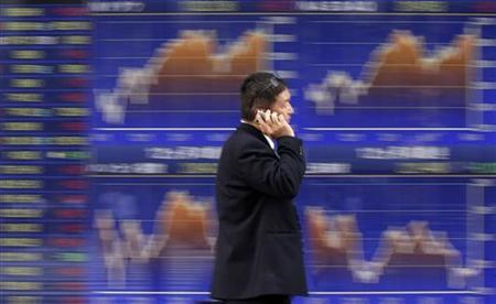 A man walks past a stock quotation board outside a brokerage in Tokyo September 12, 2012. REUTERS/Toru Hanai
