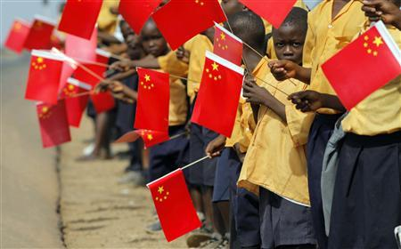 Liberian children hold Chinese flags before the arrival of China's President Hu Jintao in Monrovia in this February 1, 2007 file photo. REUTERS/Christopher Herwig/Files