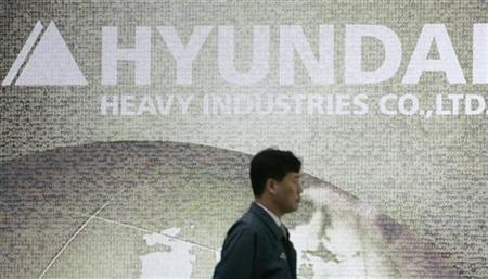 An employee of Hyundai Heavy Industries walks past its logo at the company's information centre in Ulsan, about 410 km (256 miles) southeast of Seoul, February 25, 2009. REUTERS/Jo Yong-Hak