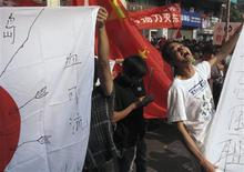 "An anti-Japan protester chants slogans beside a defaced Japanese flag, with Chinese characters reading ""Blood can be shed"" ,in the southern Chinese city of Guangzhou September 18, 2012. REUTERS/James Pomfret"