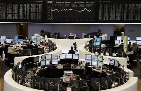 Traders are pictured at their desks in front of the DAX board at the Frankfurt stock exchange September 14, 2012. REUTERS/Remote/Amanda Andersen