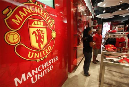 A Manchester United fan from Thailand looks inside a souvenir shop in Bangkok August 18, 2011. REUTERS/Chaiwat Subprasom