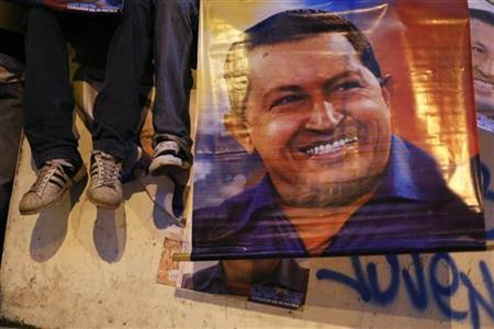 Boys sit on a fence next to a poster of Venezuelan President and presidential candidate Hugo Chavez during his campaign rally in the district of Catia in Caracas September 17, 2012. REUTERS/Jorge Silva