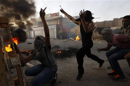 Palestinian youths throw stones towards Israeli border police (not seen) in the Shuafat refugee camp in the West Bank near Jerusalem September 18, 2012. REUTERS/Ammar Awad
