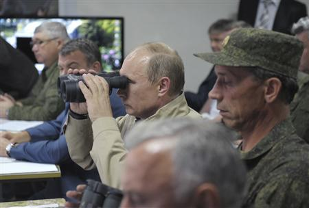 Russian President Vladimir Putin (C) uses a pair of binoculars to observe troops in action during a training exercise named Kavkaz 2012 in Krasnodar region September 17, 2012. REUTERS/Alexsey Druginyn/RIA Novosti/Pool
