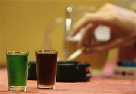 Two shots of liquor and cigarette are seen at a bar in Prague September 12, 2012. REUTERS/David W Cerny