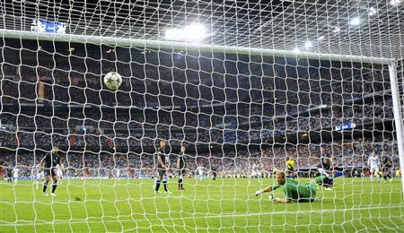 Manchester City's goalkeeper Joe Hart (R) looks at the ball as Real Madrid's Cristiano Ronaldo scores a goal during their Champions League Group D soccer match at the Santiago Bernabeu stadium in Madrid, September 18, 2012. REUTERS/Felix Ordonez