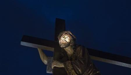 A figure of Jesus with the Cross is seen during the '''El Santo Entierro'' brotherhood procession during Holy Week in Burgos, northern Spain April 6, 2012. REUTERS/Felix Ordonez