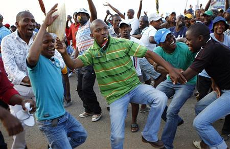 Striking miners dance and cheer after they were informed of a 22 percent wage increase offer outside Lonmin's Marikana mine, 100 km (60 miles) northwest of Johannesburg, September 18, 2012. REUTERS/Siphiwe Sibeko
