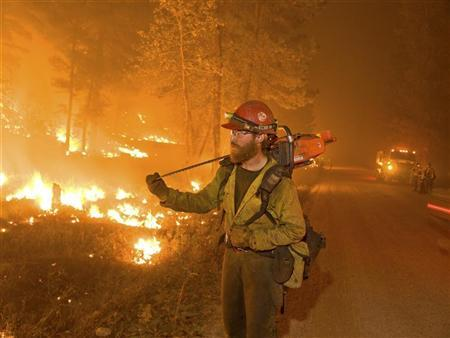 A firefighter carries a chainsaw while watching a burn operation in Boise National Forest near the community of Featherville, Idaho, in this U.S. Forest Service handout image dated August 23, 2012. REUTERS/Kari Greer/U.S. Forest Service/Handout