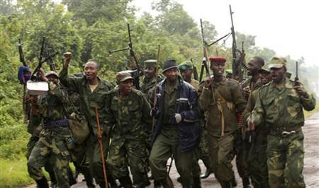 M23 rebel fighters dance in celebration in the rain at Rumangabo after government troops abandoned the town 23 km (14 miles) north of the eastern Congolese city of Goma, July 28, 2012. REUTERS/James Akena