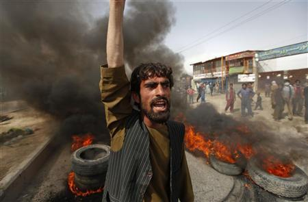 An Afghan protester shouts slogans near burning tyres during a demonstration in Kabul September 17, 2012. REUTERS/Omar Sobhani