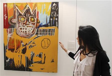 A visitor looks at ''Orange Sports Figure'' by Jean-Michel Basquiat during a contemporary arts exhibition in Doha January 25, 2012. The painting is estimated to fetch between $4,680,000 and $4,240,000 when it is auctioned off in London on February 15-16. REUTERS/Mohammed Dabbous