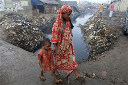 A woman and crosses a bridge with her child next to a tannery factory by the river Buriganga at Hazaribagh in Dhaka July 12, 2012. REUTERS/Andrew Biraj/Files