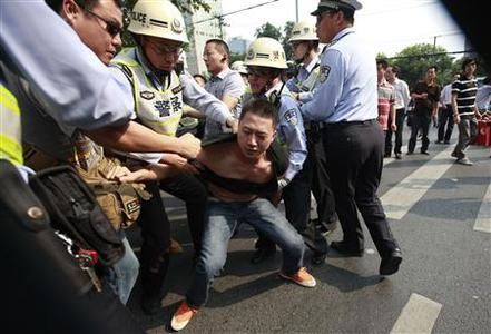 A demonstrator scuffles with policemen during a protest near the Japanese consulate on the 81st anniversary of Japan's invasion of China, in Shanghai September 18, 2012. REUTERS/Aly Song