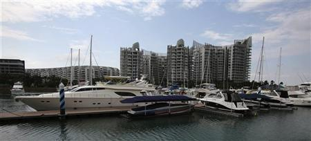 Yachts berthed at the One Degree 15 Marina Club are seen against a condominium complex at Sentosa Cove in Singapore April 25, 2012. REUTERS/Tim Chong