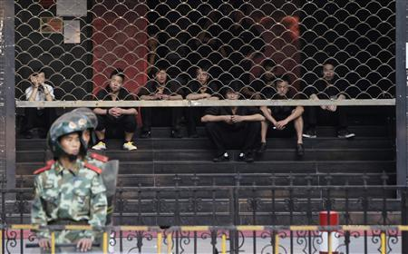 Paramilitary policemen stand guard as waiters sit behind barriers in front of a Japanese restaurant on the 81st anniversary of Japan's invasion of China, in Shanghai, September 18, 2012. REUTERS/Aly Song
