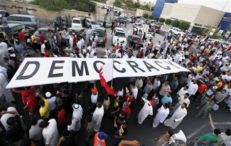 Protesters carry a large banner reading: ''Democracy'' as they participate in an anti-government protest in Budaiya highway, west of Manama, September 14, 2012. REUTERS/Hamad I Mohammed