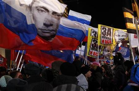 Supporters of Russia's current Prime Minister and presidential candidate Vladimir Putin wave flags during a raly in his support in Manezhnaya Square near the Kremlin in central Moscow March 4, 2012. Reuters/Mikhail Voskresensky