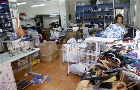 Employees work at a clothes repair shop in Madrid August 29, 2012. Hard times are forcing Spaniards to overcome their love of the new; for the first time in a generation, many are learning to fix things when they break - and even to bu y goods second hand. Picture taken August 29, 2012. REUTERS/ Sergio Perez
