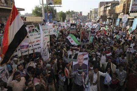 People hold pictures of victims at a rally in Sanaa September 18, 2012, commemorating people killed during last year's unrest against former Yemeni president Ali Abdullah Saleh. Tuesday marked the first anniversary of a major clash between opposition protesters and Saleh's security forces, which saw at least 26 people shot dead and hundreds wounded. REUTERS/Mohamed al-Sayaghi