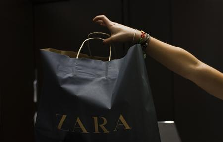 A customer grabs her purchase at a Zara store in Madrid September 19, 2012. The world's largest clothing retailer, Zara owner Inditex, posted a 32 percent jump in first-half year profit on Wednesday, beating expectations, boosted by rapid expansion to fast-growing emerging markets. REUTERS/Susana Vera