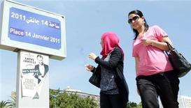 "Women walk past a poster of the play ""Made in Tunisia, 100 percent halal"" by Tunisian actor and playwright Lotfi Abdeli in Tunis September 18, 2012. A few hours before Abdeli was due to stage his play ""Made in Tunisia, 100 percent halal"" last month, hundreds of Salafi Muslims who believed the show was offensive to Islam occupied the open air theatre and began to pray. The play, a satire about politics and religion, was cancelled. It was not the first time religious hardliners have stopped the plays of Abdeli, a Tunisian actor and playwright known for criticising ousted president Zine El Abidine Ben-Ali before last year's revolution. Picture taken September 18, 2012. To match Feature TUNISIA-SALAFI/ART REUTERS/Zoubeir Souissi"