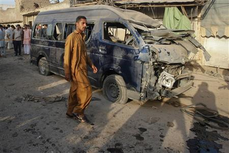 A resident walks past a damaged vehicle at the site of a bomb attack on the outskirts of Peshawar September 19, 2012. A bomb in Peshawar killed at least 10 people and wounded more than 30 on Wednesday, police said. The bomb seemed to be targeting a van carrying officials from the Pakistan Air Force, said a local police official. REUTERS/Fayaz Aziz