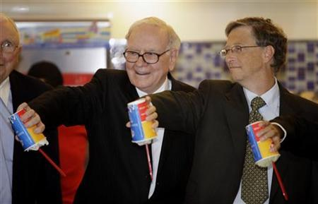 Billionaires Warren Buffett (L) and Bill Gates pose for a photo while each holding a cup of DQ ice cream upside down during their visit to a new Dairy Queen store in Beijing September 30, 2010. REUTERS/Jason Lee/Files