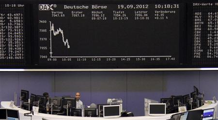 A trader stands in front of his desk below the DAX board at the Frankfurt stock exchange September 19, 2012. REUTERS/Remote/Lizza May David