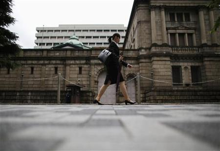 A woman walks past the Bank of Japan headquarters in Tokyo July 2, 2012. REUTERS/Toru Hanai/Files