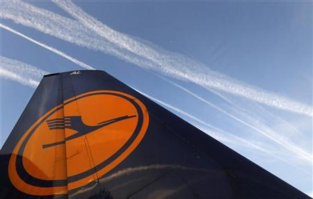 Air planes fly over the Fraport airport, next to a Lufthansa aircraft tail fin, in Frankfurt, September 4, 2012. REUTERS/Kai Pfaffenbach