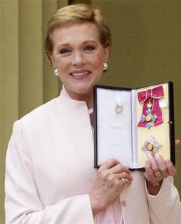 Dame Julie Andrews, star of Mary Poppins and the Sound of Music, shows off her award after receiving the honour of Dame Commander of the Order of the British Empire from the Queen at Buckingham Palace, May 16, 2000. REUTERS/POOL Old