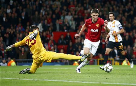 Manchester United's Michael Carrick (C) goes past Galatasaray's Fernando Muslera (L) to score during their Champions League Group H soccer match at Old Trafford in Manchester, northern England, September 19, 2012. REUTERS/Darren Staples