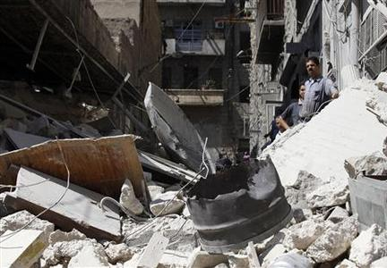 Civilians stand on rubble as they inspect the damage caused by a jet's strike in the al-Kalaseh neighbourhood in Aleppo September 19, 2012. REUTERS/Zain Karam