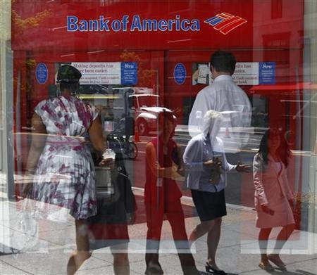 Pedestrians are reflected in the window as customers conduct transactions at a Bank of America ATM in Washington July 19, 2011. REUTERS/Kevin Lamarque