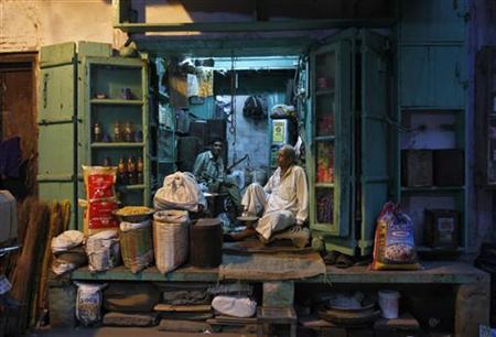 A shopkeeper (R) and his sales assistant wait for customers inside a family-owned grocery store in an alley in the old quarters of Delhi September 17, 2012. Thousands of kirana, or general store, owners planned to close their shops on Thursday to protest against a government decision to allow in foreign supermarkets such as Wal-Mart Stores Inc. They fear the move could lead to the destruction of the ubiquitous family-owned stores that occupy a central place in Indian daily life and help give the country the highest shop density in the world. Picture taken September 17, 2012. REUTERS/Mansi Thapliyal