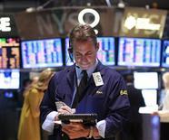 Трейдер работает в торговом зале биржи в Нью-Йорке, 18 сентября 2012 года. Американские акции выросли в среду благодаря хорошим показателям рынка жилья. REUTERS/Brendan McDermid