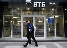 Молодые люди проходят мимо отделения банка ВТБ в Санкт-Петербурге, 16 сентября 2008 года. Второй по величине госбанк РФ ВТБ пока не меняет прогноз чистой прибыли на 2012 год, но будет учитывать ожидания рынка, сказал на брифинге финансовый директор банка Герберт Моос. REUTERS/Alexander Demianchuk